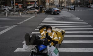 A courier waits for business at a normally busy intersection in Beijing on Friday.