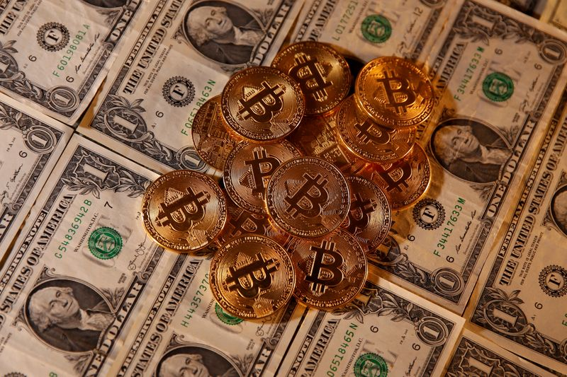 © Reuters. FILE PHOTO: Representations of virtual currency Bitcoin and U.S. dollar banknotes are seen in this picture illustration