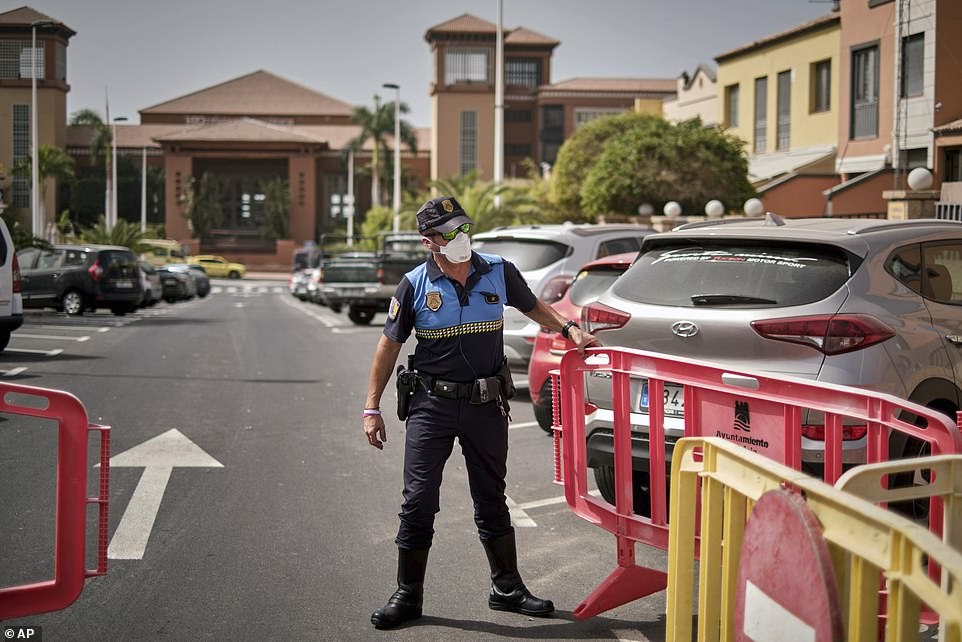 A Spanish police officer sets up a barrier blocking the road to the H10 Costa Adeje Palace hotel in Tenerife yesterday as the complex was locked down over coronavirus fears