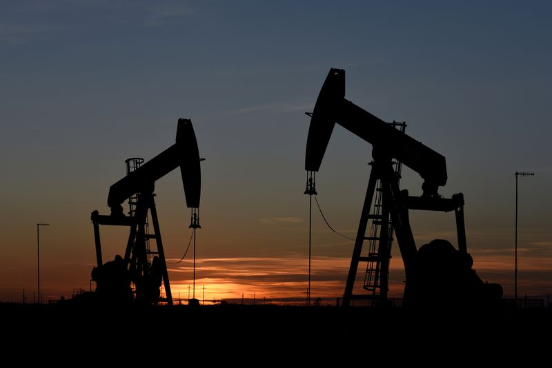 © Reuters. FILE PHOTO: Pump jacks operate at sunset in an oil field in Midland