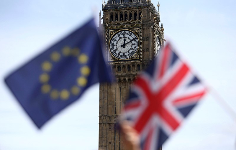 © Reuters. Participants hold a British Union flag and an EU flag during a pro-EU referendum event at Parliament Square in London