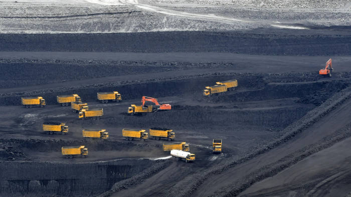 CHANGJI, CHINA - JULY 04: Transport trucks transfer raw coal in pits as deep as 200 meters at the East Junggar Basin on July 4, 2018 in Changji Hui Autonomous Prefecture, Xinjiang Uyghur Autonomous of China. The East Junggar Basin as one of the largest coalfield in Xinjiang has predicted coal reserves of 390 billion tons. (Photo by Liu Xin/China News Service/Visual China Group via Getty Images)