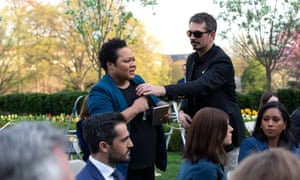 A White House aide attempts to take the microphone out of the hands of correspondent Yamiche Alcindor as she questions Donald Trump.