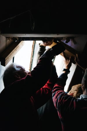 A group of volunteers perform maintenance on a bothy window.