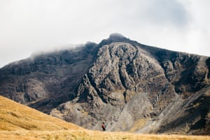 A lone walker in mountainous Scottish countryside.