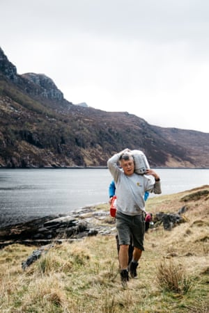 A bothy volunteer carries building materials on his back.