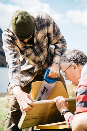 Two volunteers cut wood to measure in order to make new seating for a Scottish bothy.