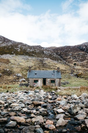 Materials rest on the front of the building as volunteers carry on their repair work on a bothy roof.